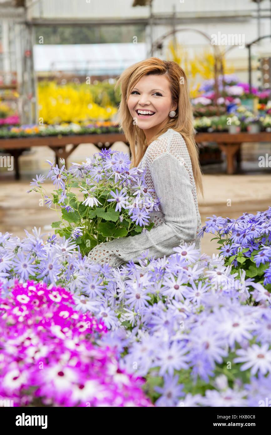 Pretty young woman enjoying spring garden center Stock Photo