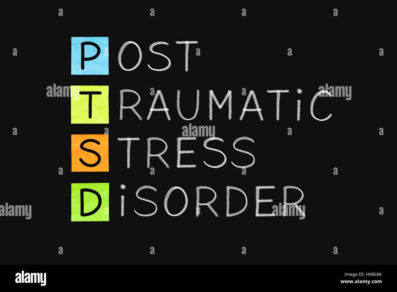 PTSD acronym Post Traumatic Stress Disorder handwritten with white chalk on blackboard. - Stock Image