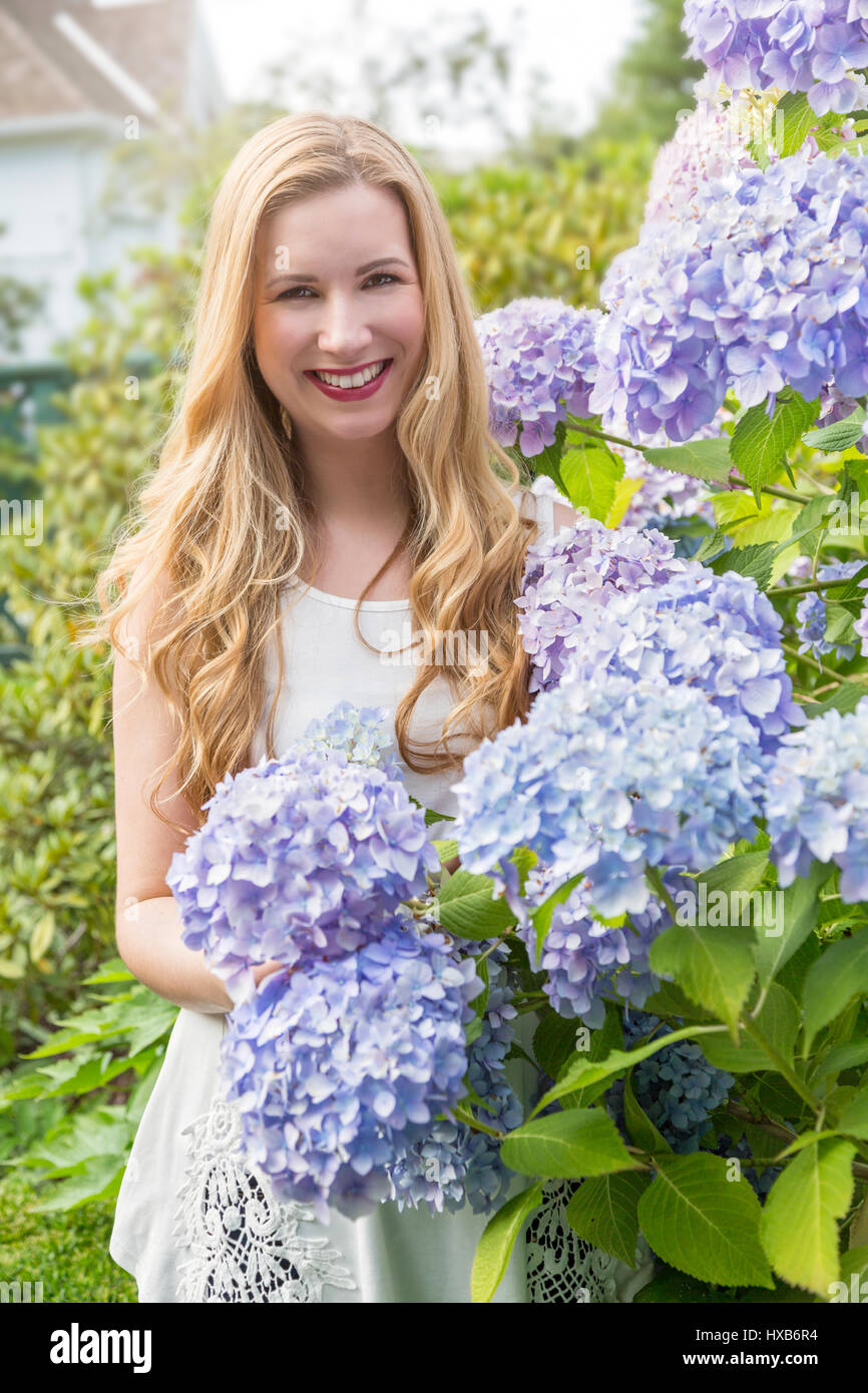 Happy young woman enjoying a summer flower garden Stock Photo