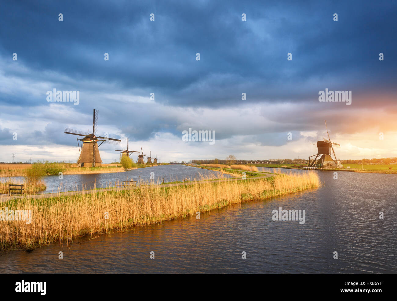 Amazing windmills. Rustic landscape with traditional dutch windmills near the water canals and blue cloudy sky and - Stock Image