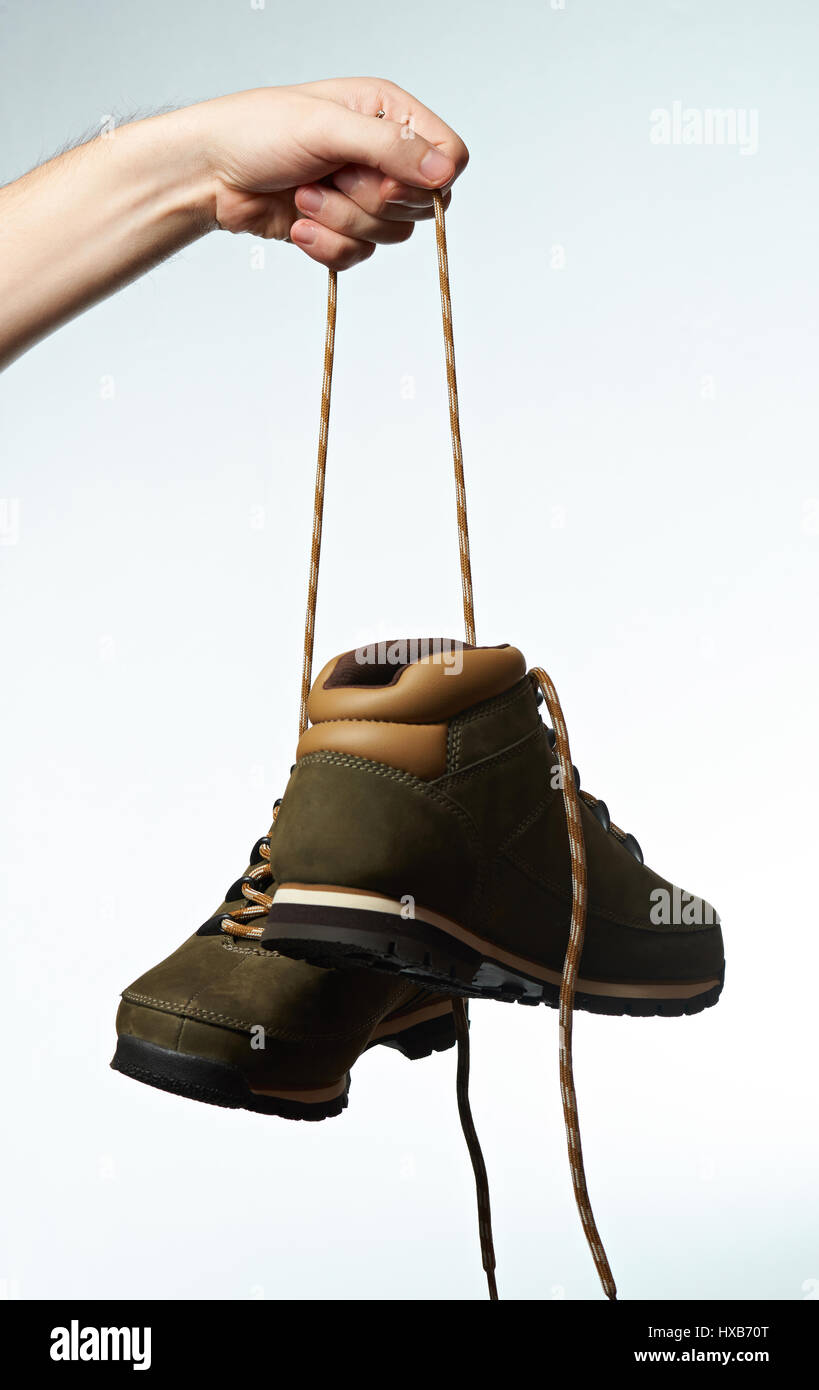 Hiking boots hang on laces isolated on white background
