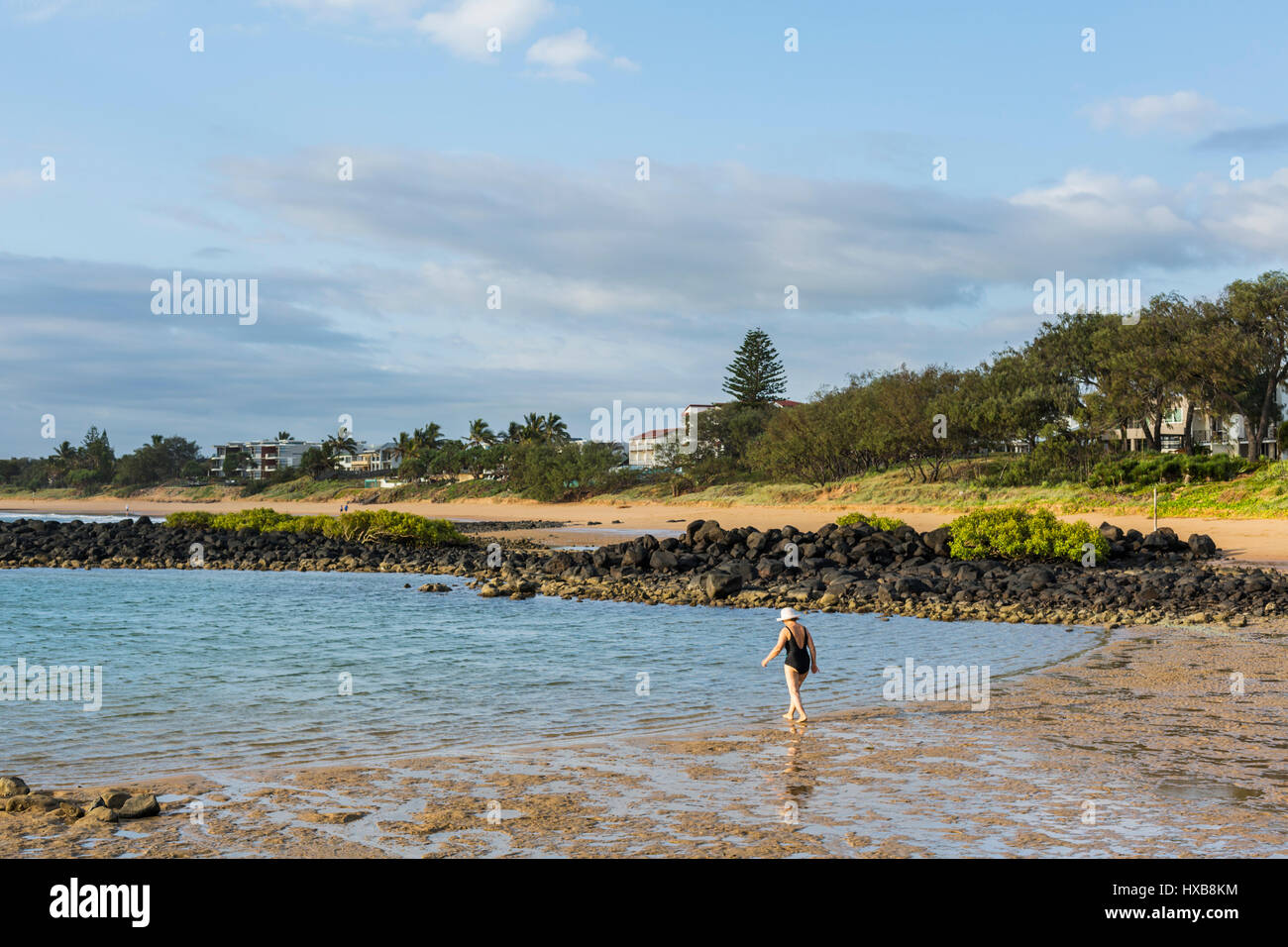 Woman walking into the sea at Bargara Beach, Bundaberg, Queensland, Australia - Stock Image