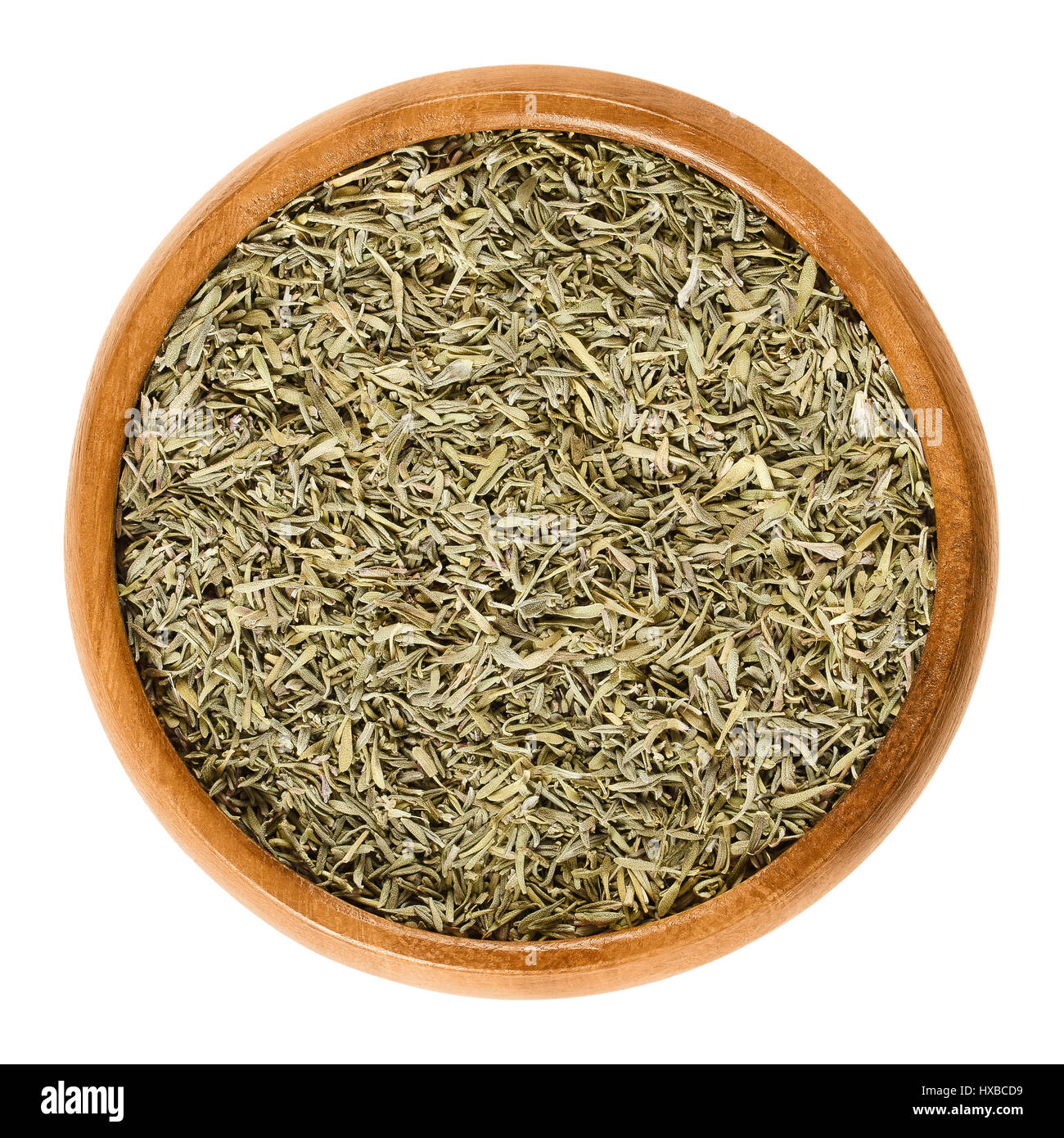 Dried thyme in wooden bowl. Minced stems. Herb with culinary and medicinal uses. Thymus vulgaris is a relative of - Stock Image