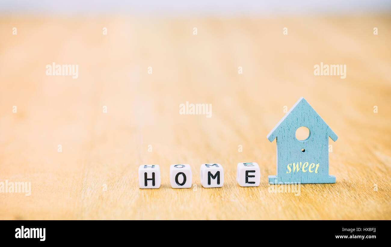 HOME Sweet horizontal word of cube letters behind blue house symbol on wooden surface - Stock Image