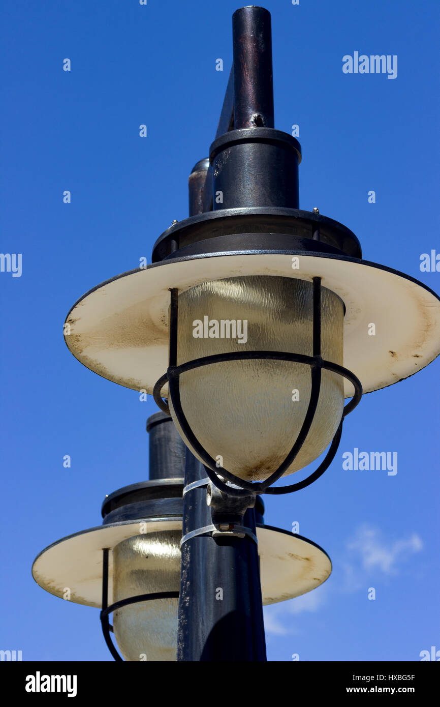 Weathered pier lights stand out against the bright blue Caribbean sky. - Stock Image