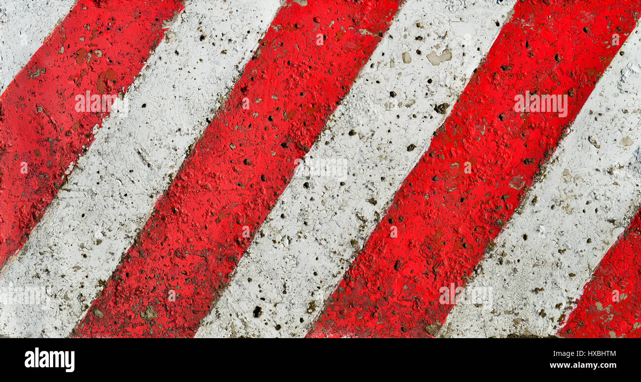 Diagonal red white lines paint pattern on a rough textured cement