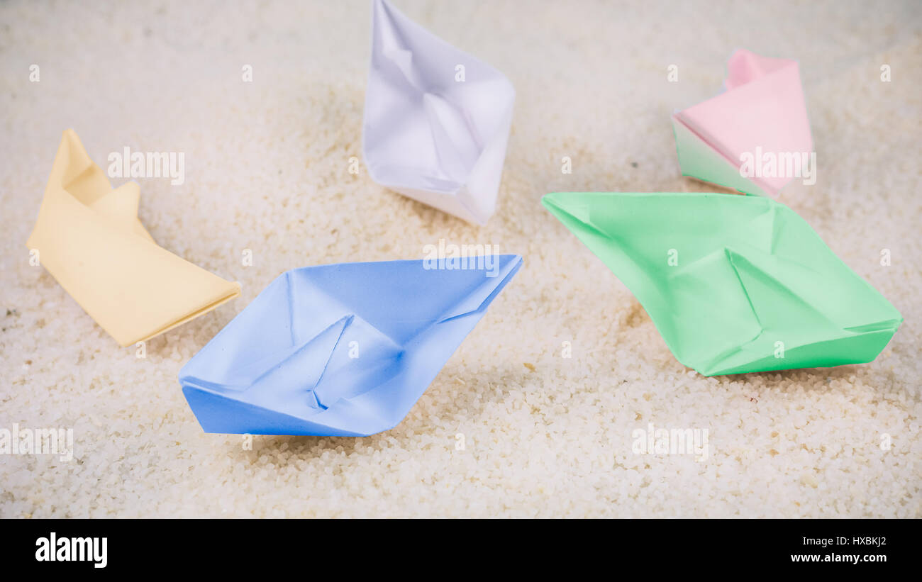 Coloured Paper Ships Chaotic Laying on Sandy in the Desert Stock Photo