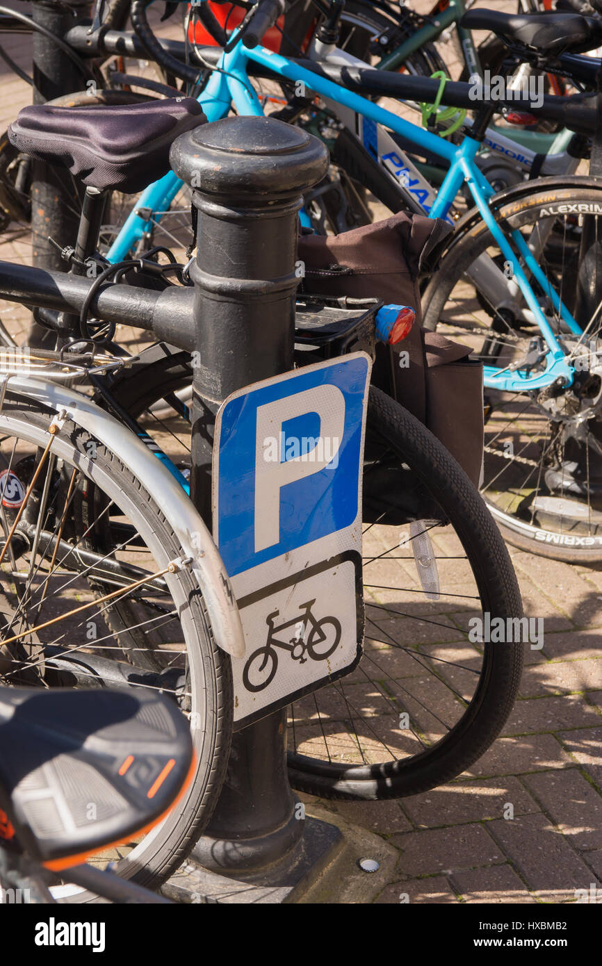 Bike parking sign and monitored storage area in the city centre provided for cyclists - Stock Image
