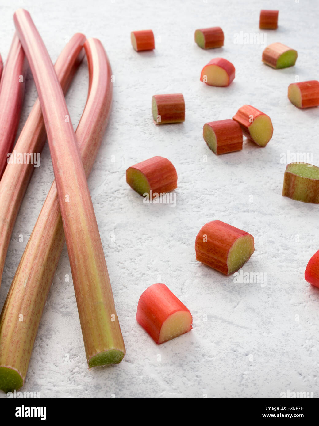 Fresh rhubarb and cut pieces of rhubarb on textured white marbled background. Shallow depth of field. - Stock Image