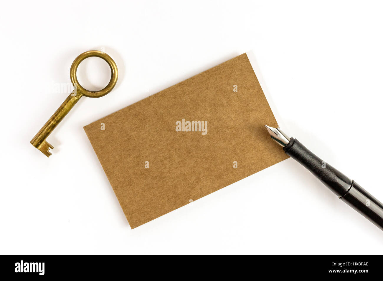 A photo of a kraft paper business card with an ink pen and a vintage a photo of a kraft paper business card with an ink pen and a vintage key on a white background a mockup or a minimalist banner with copy space reheart Gallery