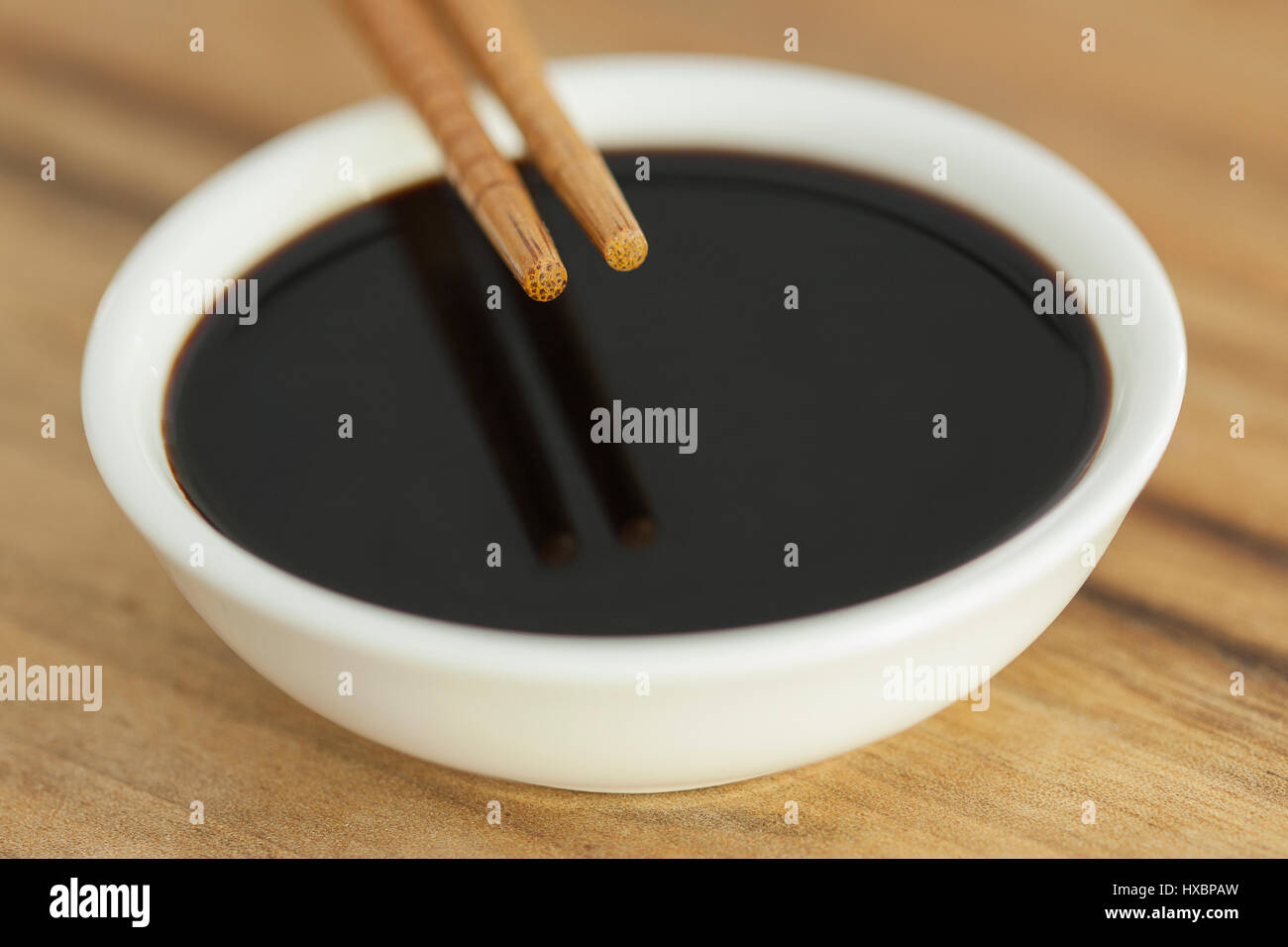 Close-up of  soy sauce with mirror chop sticks. - Stock Image