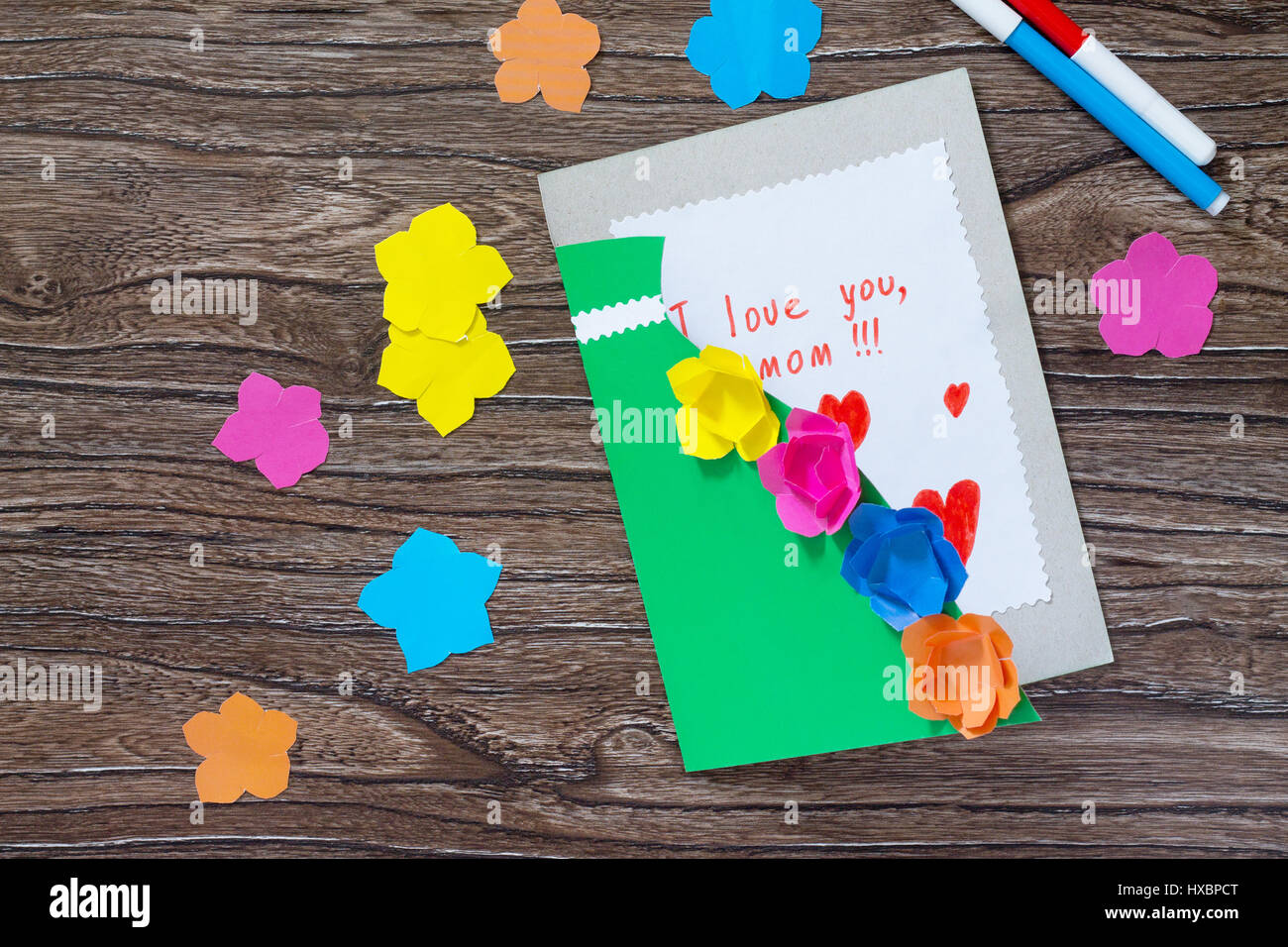 A Child Is Holding A Greeting Card With Flowers On Mother S Day