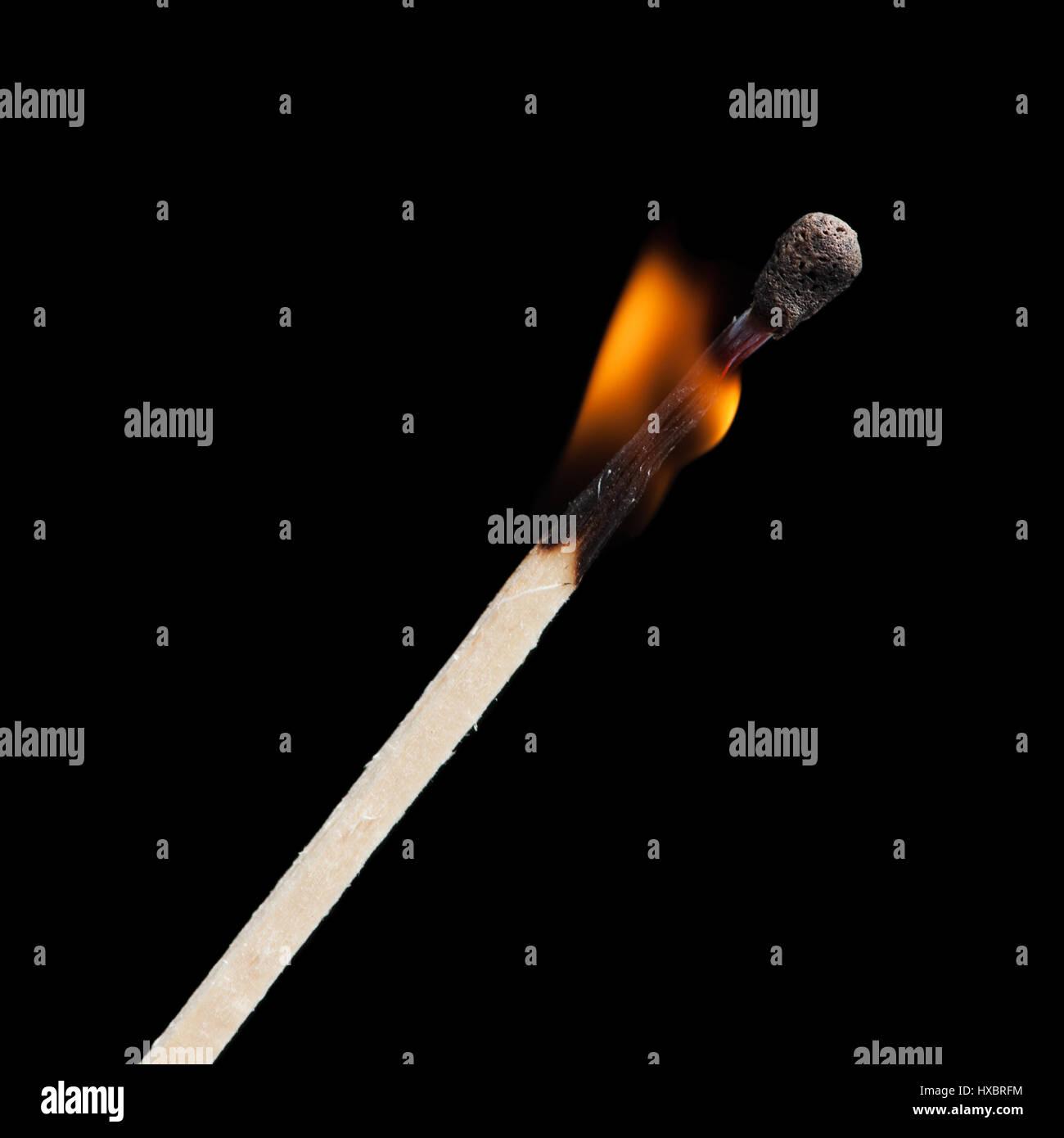 Burning match on black background - Stock Image