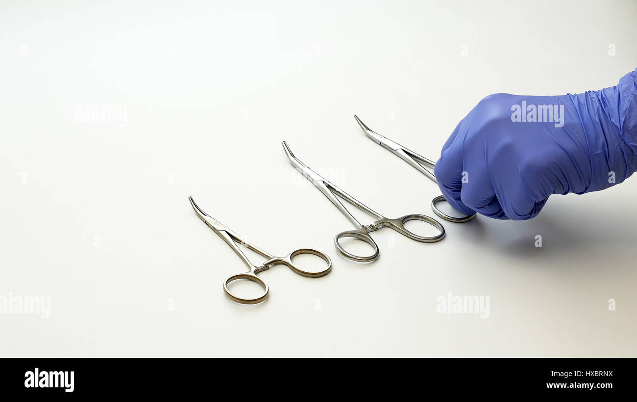Surgical nurse puts medical surgery tools on table - Stock Image