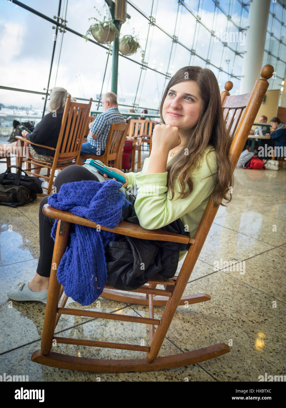 A girl sits on a rocking chair in the Pacific Marketplace of the Central Terminal of Seattle-Tacoma International - Stock Image