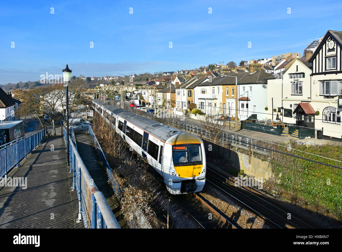Trenitalia c2c train with National Express markings passing close to houses in residential street in seaside town - Stock Image