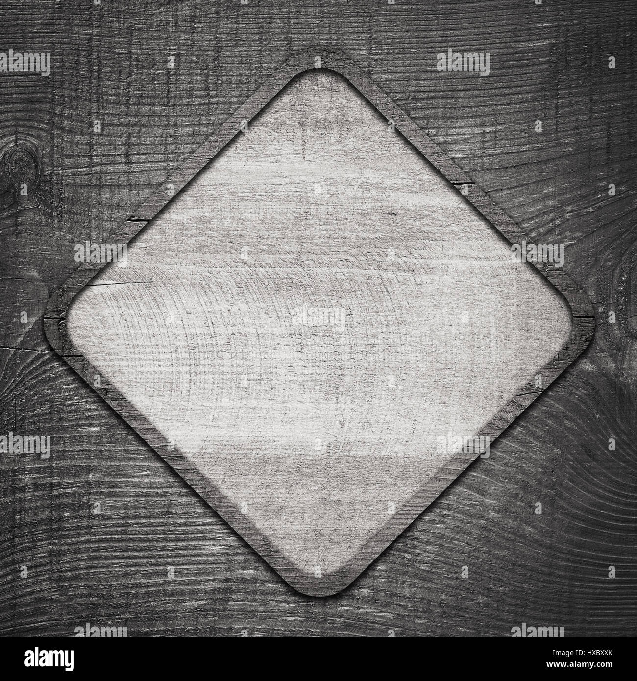 Gray wooden lozenge with frame on dark wall - Stock Image