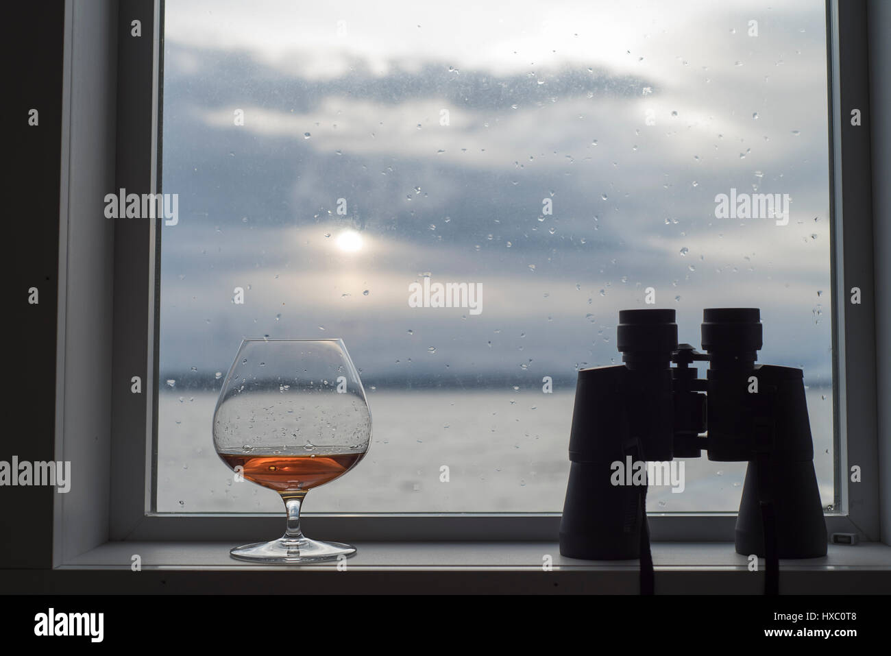 Brandy snifter glass in window with binoculars Stock Photo