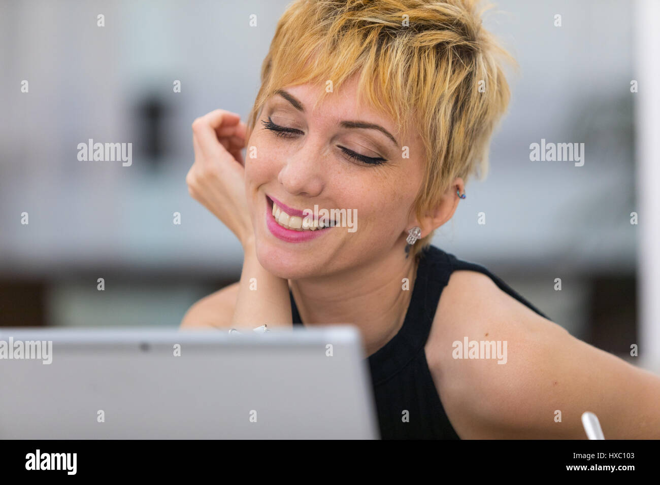 woman in a bar flirting or chatting in a video conference call, concept of online dating or conference - Stock Image