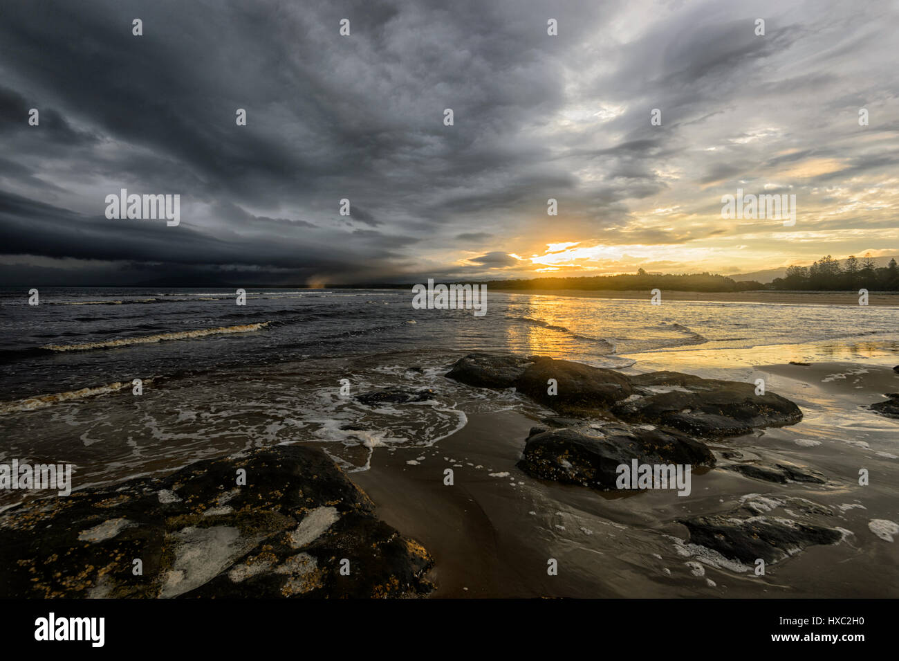 Dramatic sunset with black threatening clouds over Seven Mile Beach, Gerroa, Illawarra Coast, New South Wales, NSW, - Stock Image