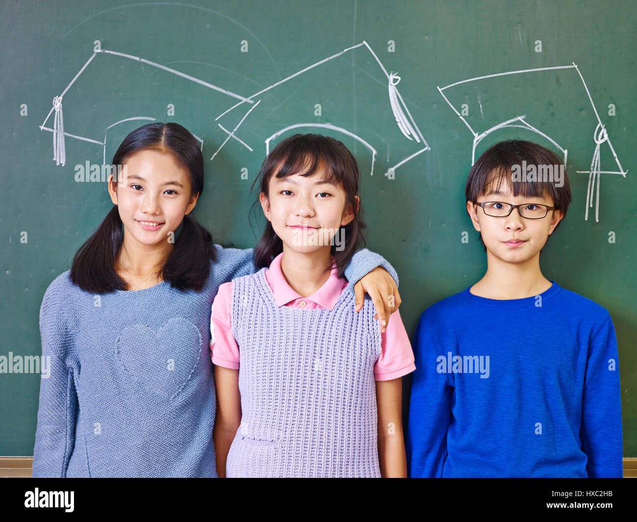 three asian elementary school children standing in front of chalkboard underneath chalk-drawn doctoral caps. - Stock Image