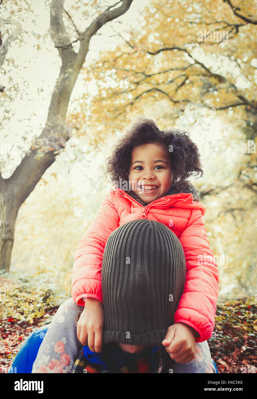 Portrait smiling daughter pulling stocking cap over fathers head in autumn  park 09c87cd05f8