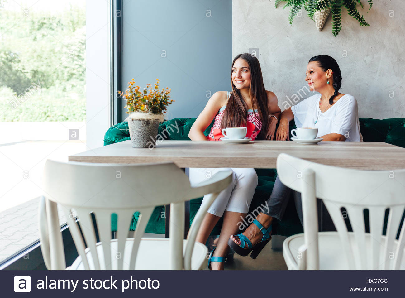 Two happy women in cafe. Aged woman and her adult daughter drinking coffee and looking through the window in a cafe. - Stock Image