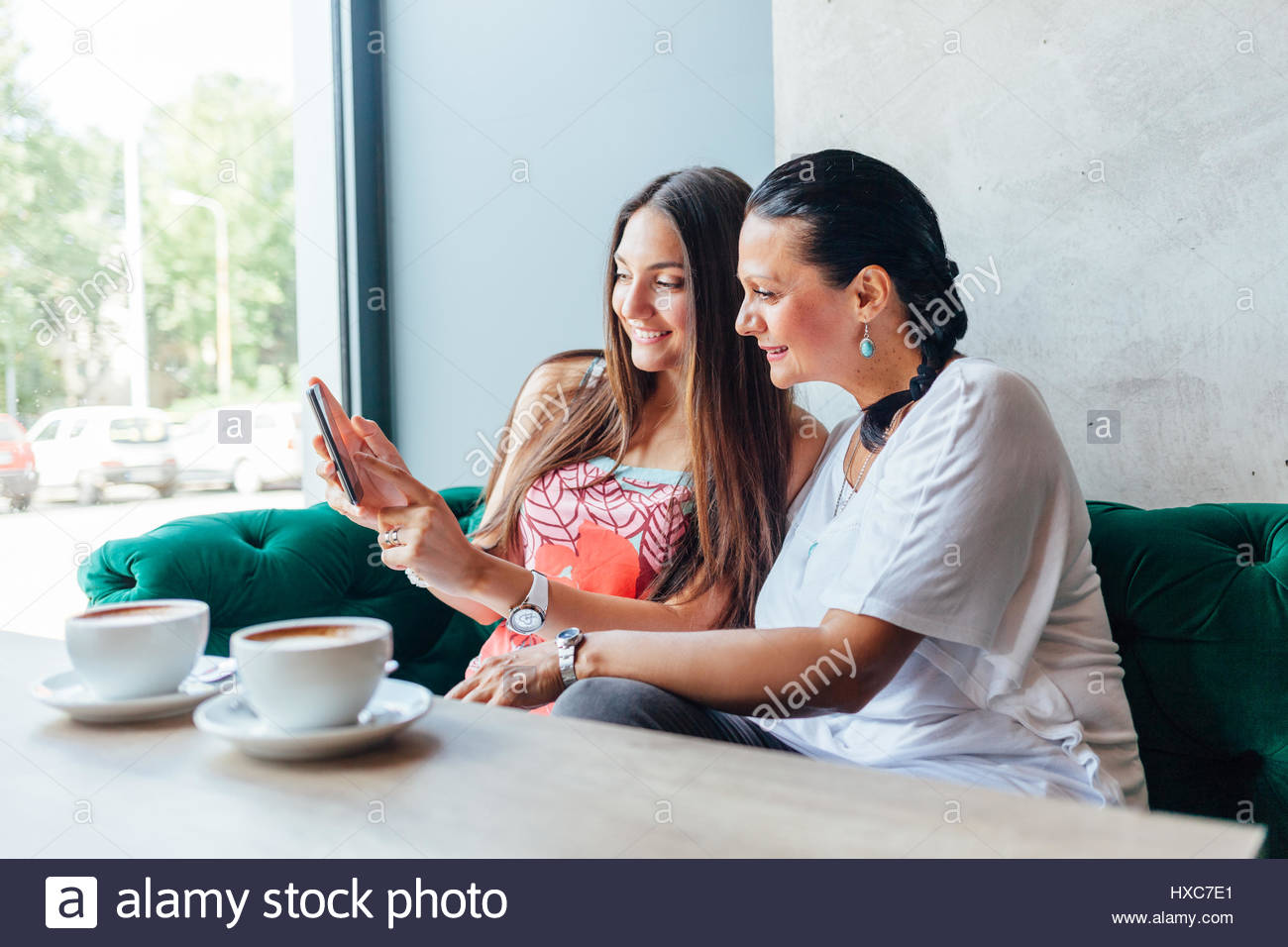 Mother and daughter women using a mobile phone in a cafe - Stock Image