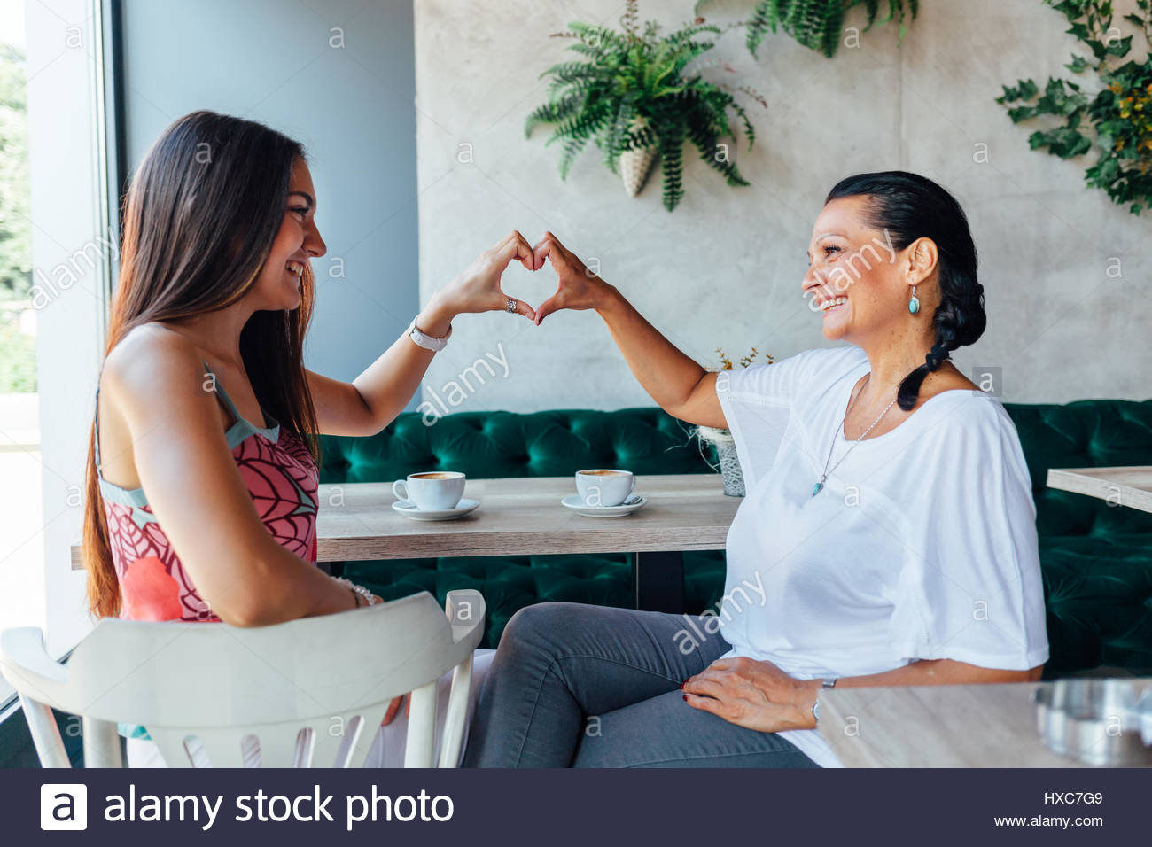 Mom and daughter making a heart with hands. Love coffee. - Stock Image