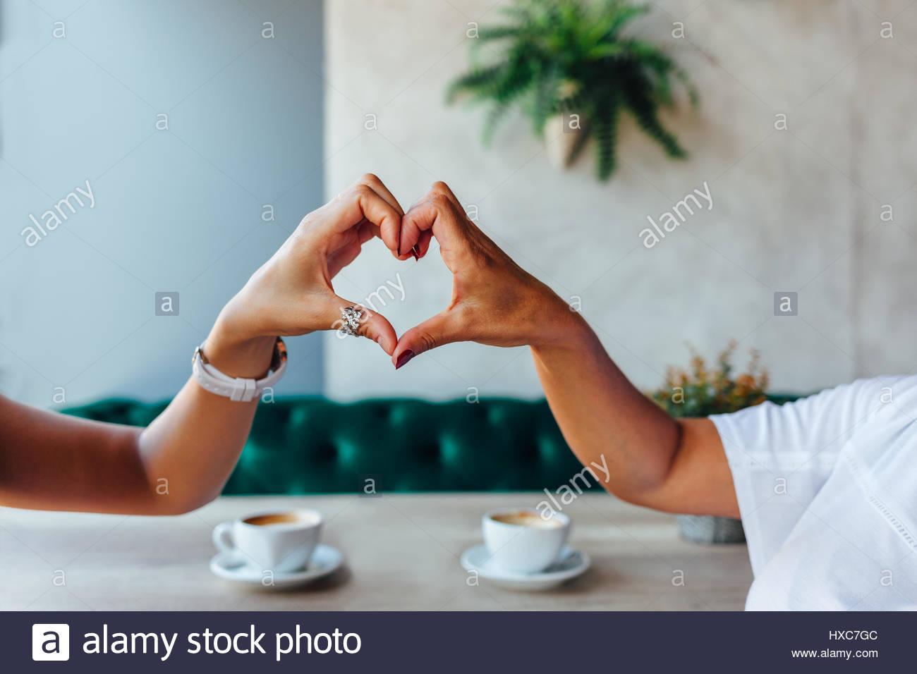 Closeup of mom and daughter making a heart with hands - Stock Image
