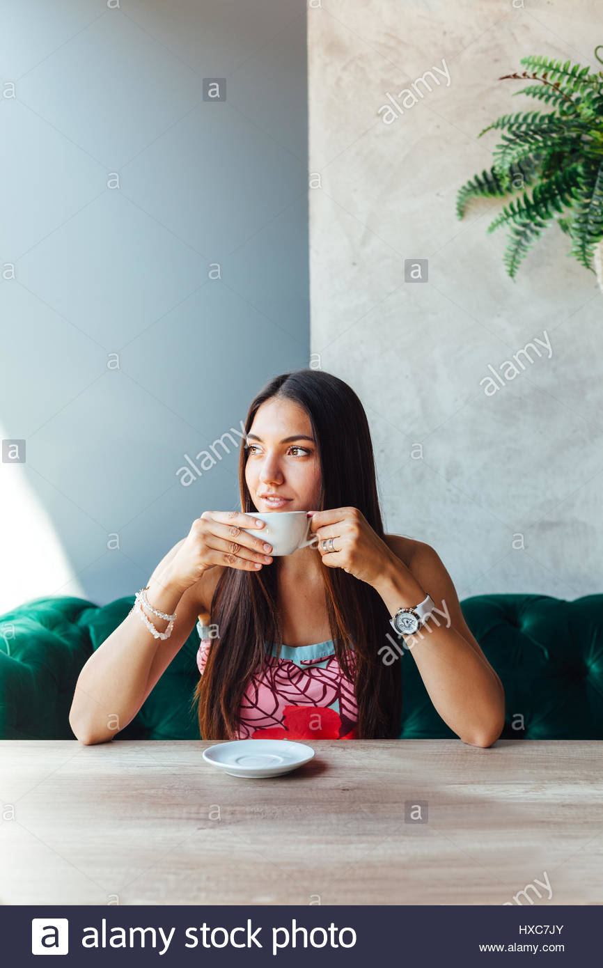 Portrait of beautiful young woman in a cafe - Stock Image