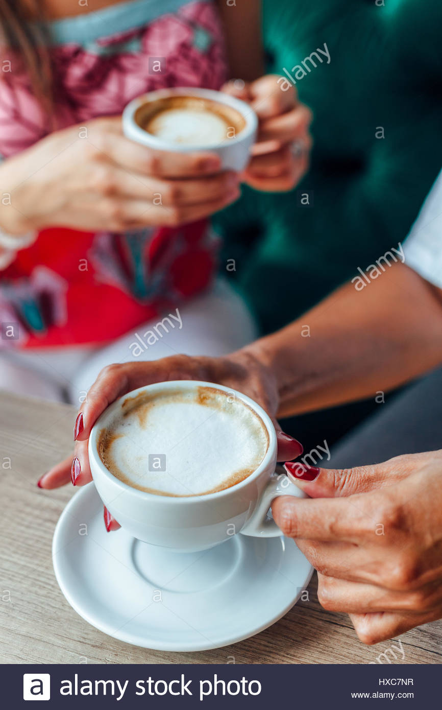 Mother and daughter enjoying the smell and taste of coffee - Stock Image
