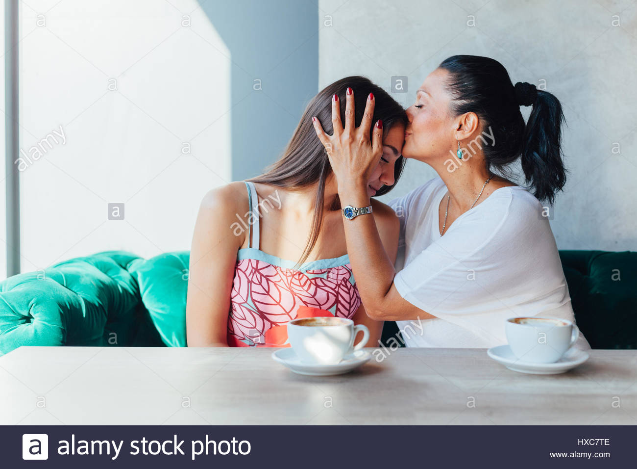 Mother kissing daughter in a cafe - Stock Image
