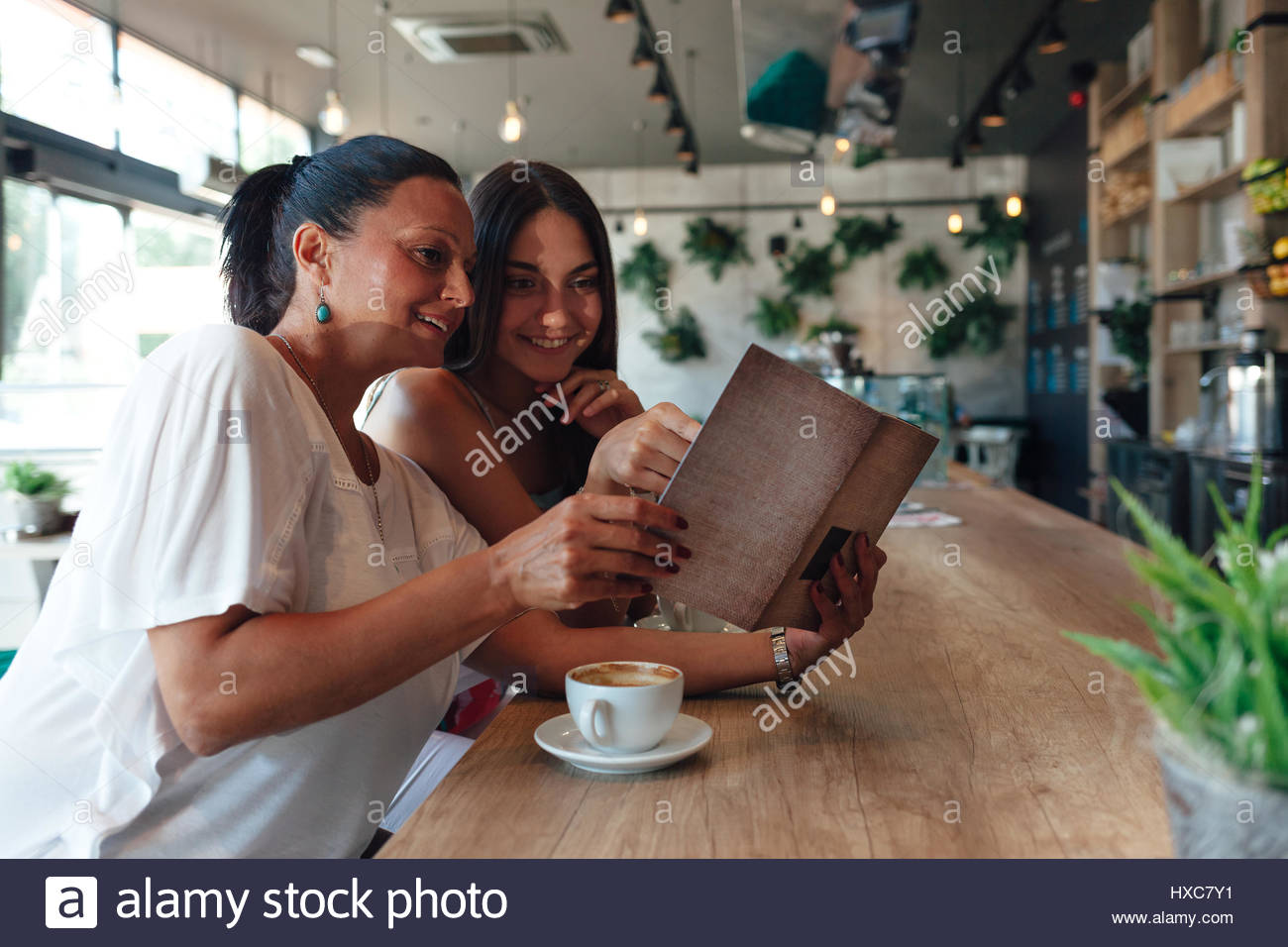 Mother and daughter drinking coffee and looking at cafe menu - Stock Image