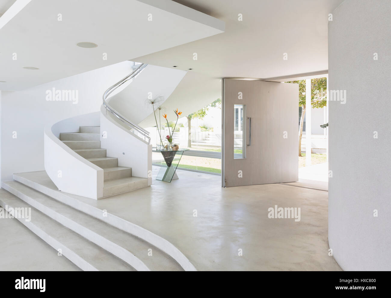 White foyer and spiral staircase in modern luxury home showcase ...
