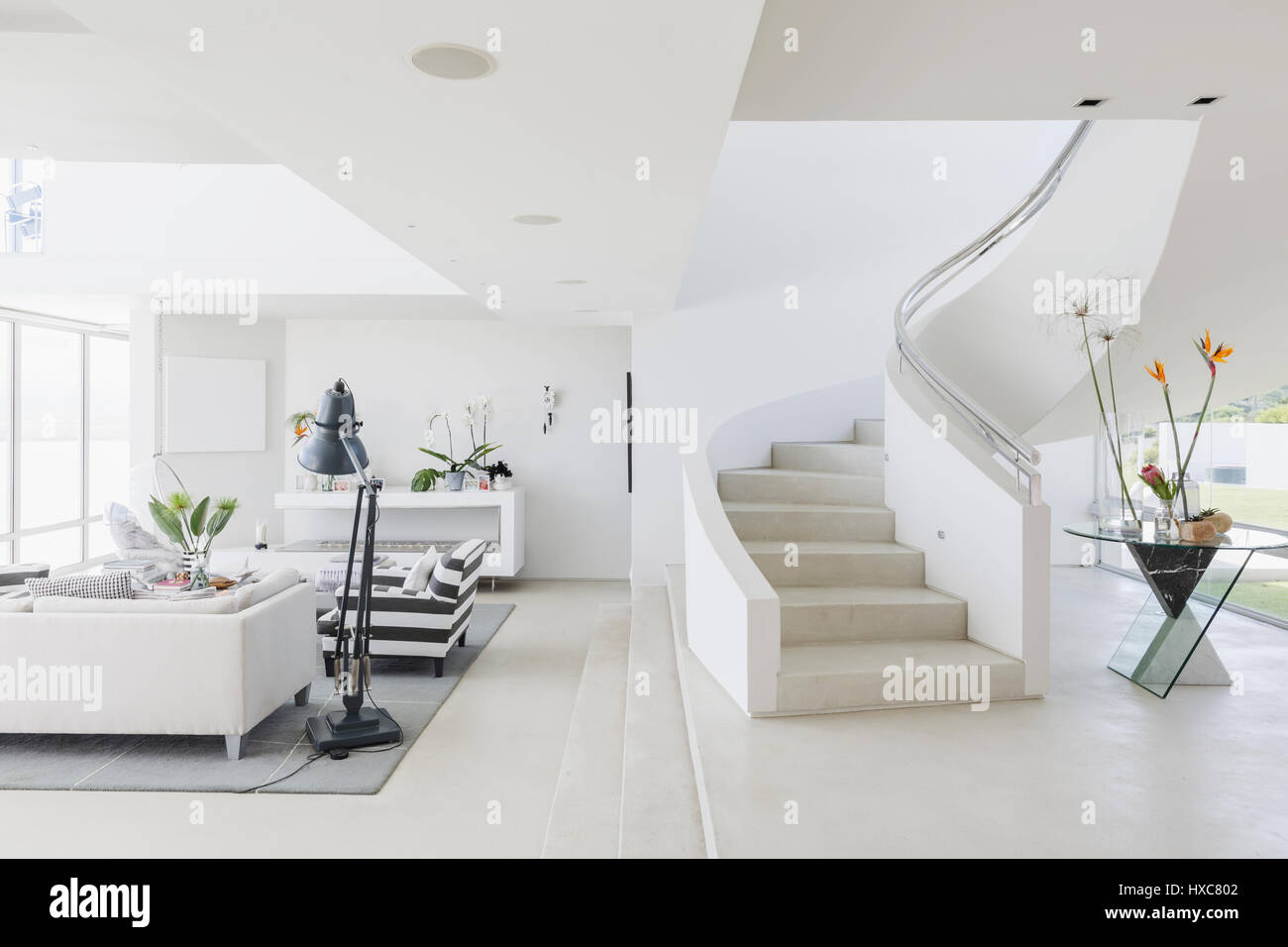 White modern luxury home showcase spiral staircase and living room ...