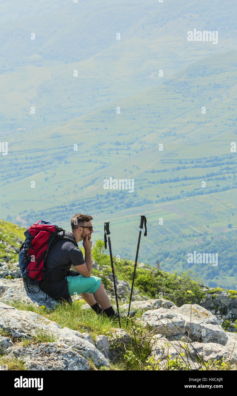 Image of a hiker resting on rocks and looking in the