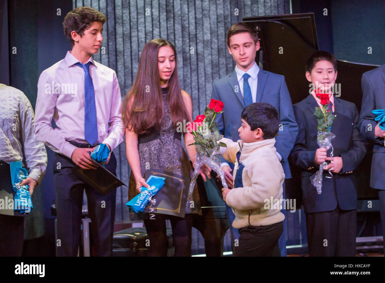 Commerce Township, Michigan - High school students are given roses for raising funds for children affected by war Stock Photo
