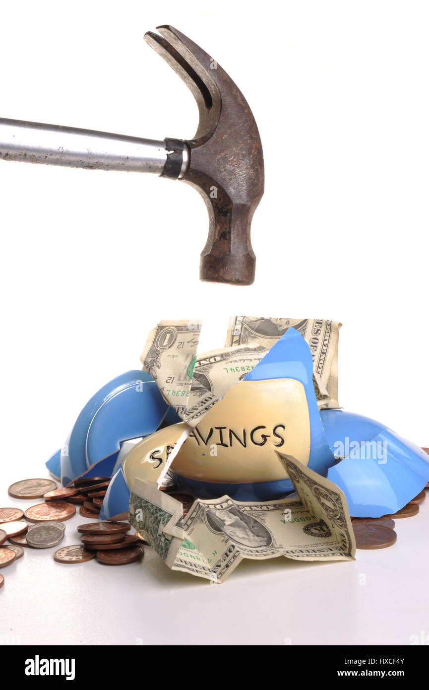Breaking a money box with a hammer with dollar notes falling out - Stock Image