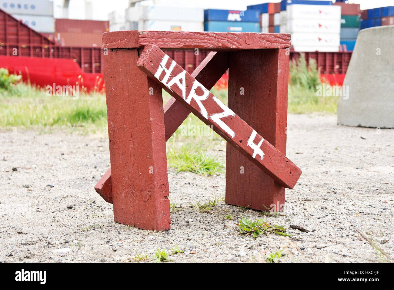 'A self-made stool before a container ship with the label ? ? ? resin 4? ? ?, A self-timbered stool in performs - Stock Image