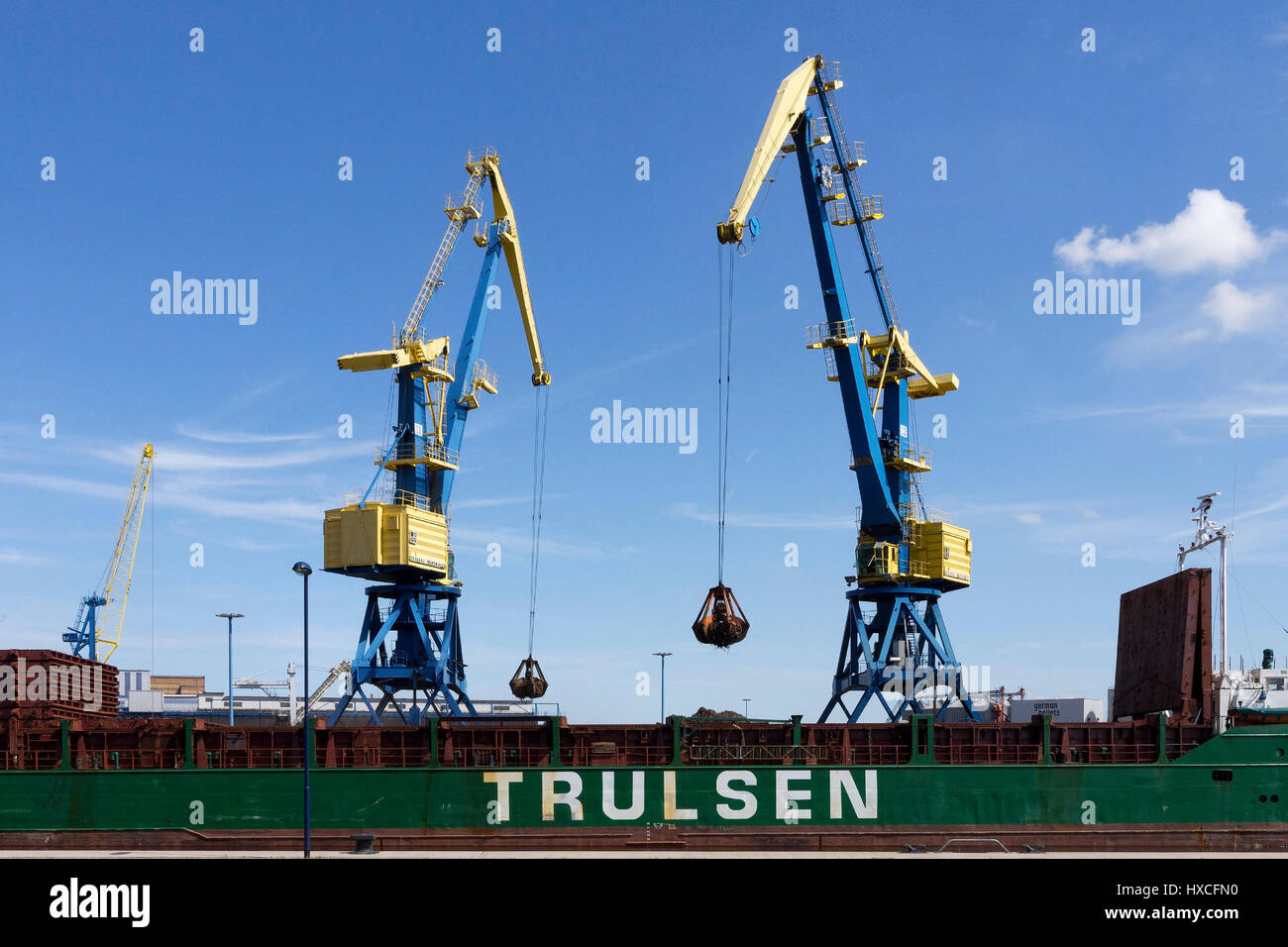 Two cranes unload a freighter in the harbour of the Hanseatic town Wismar, Two cranes unload a freighter in the - Stock Image