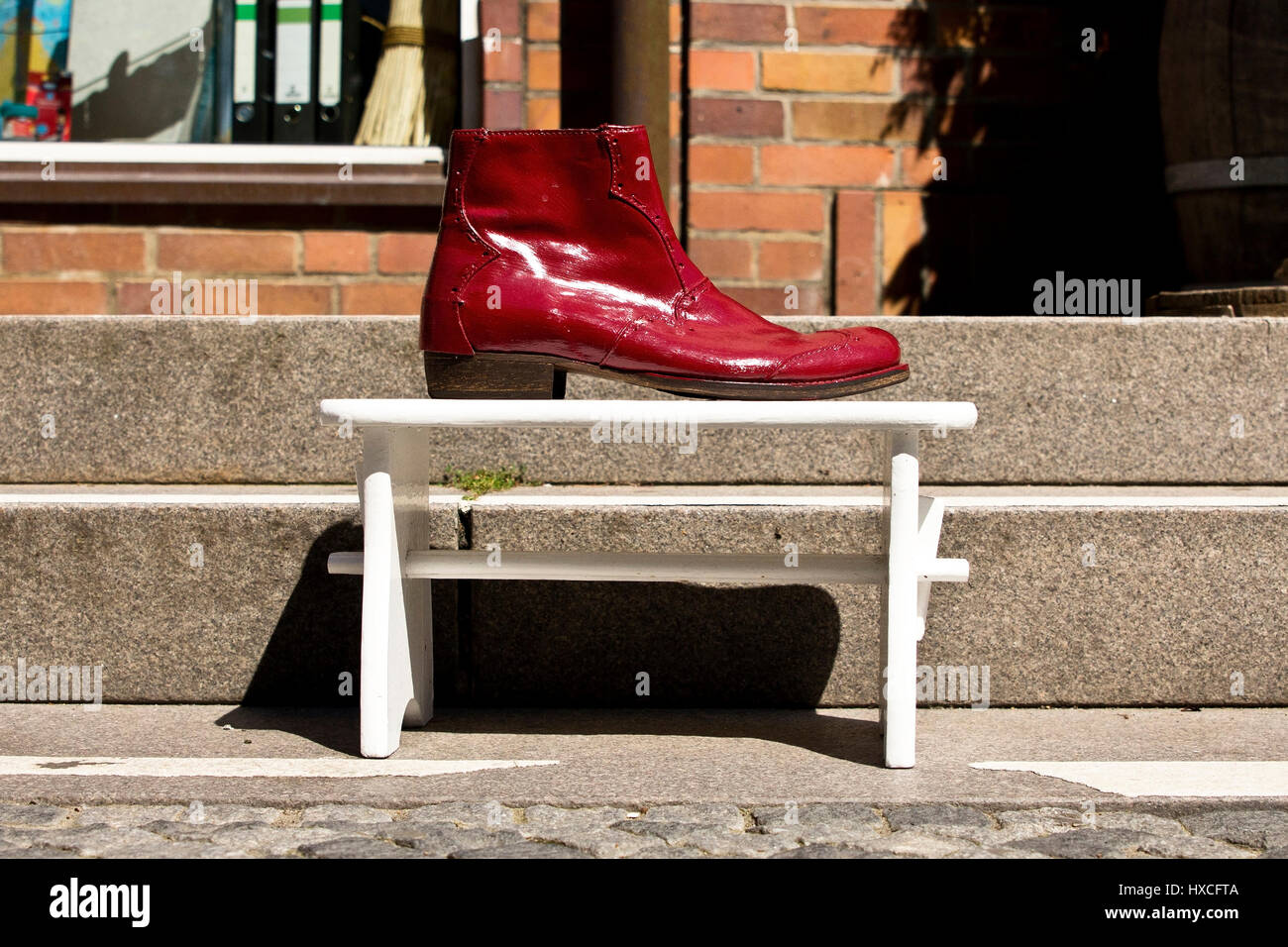 A red patent leather shoe on a white wooden stool before a business, A red clever leather shoes on a white wooden - Stock Image