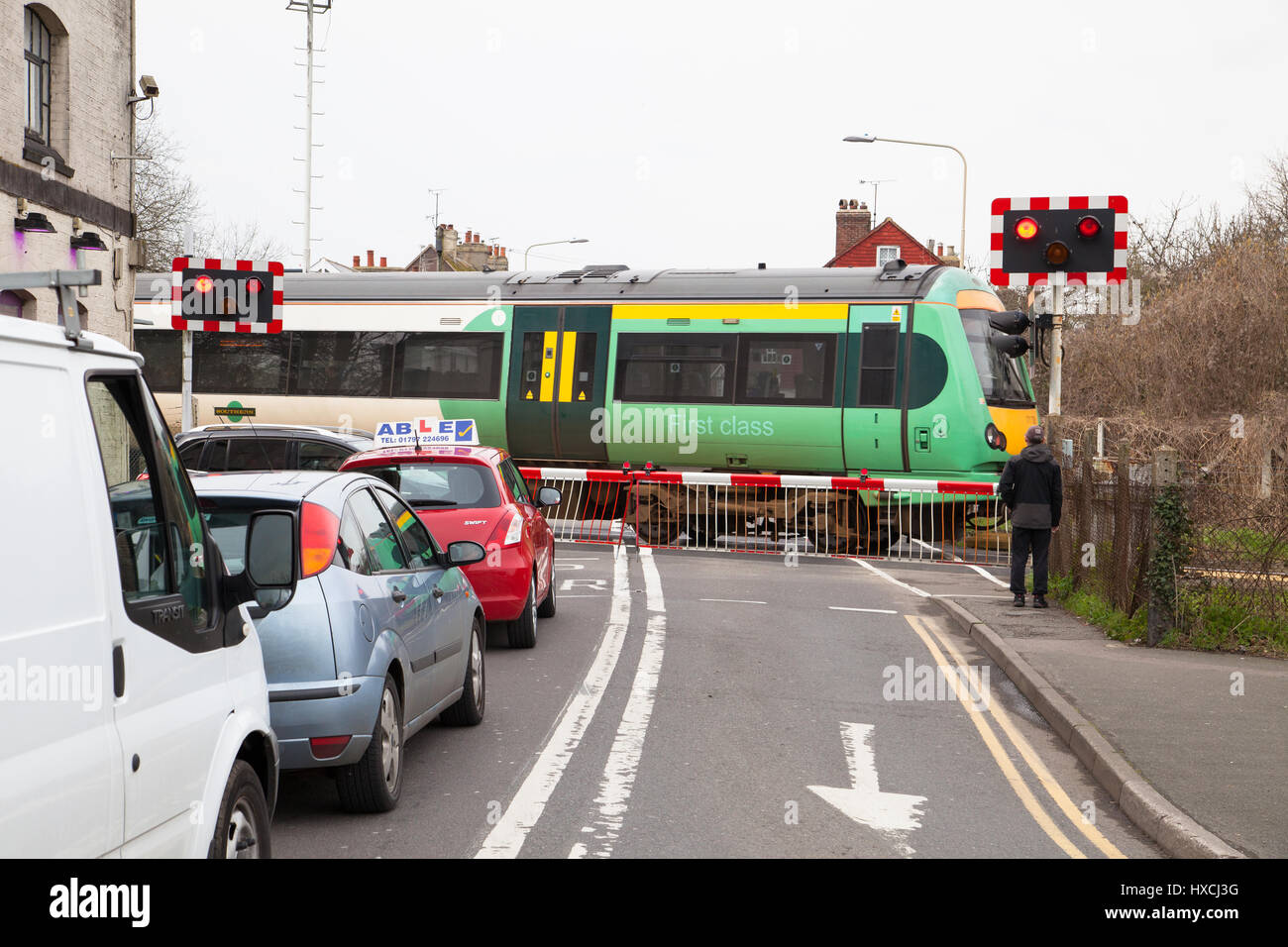 Railway barriers closed southern railway train crossing cars and pedestrian waiting Rye East Sussex - Stock Image
