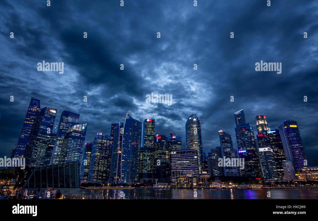 Moon light shinning through clouds over the city scape of Singapore. - Stock Image