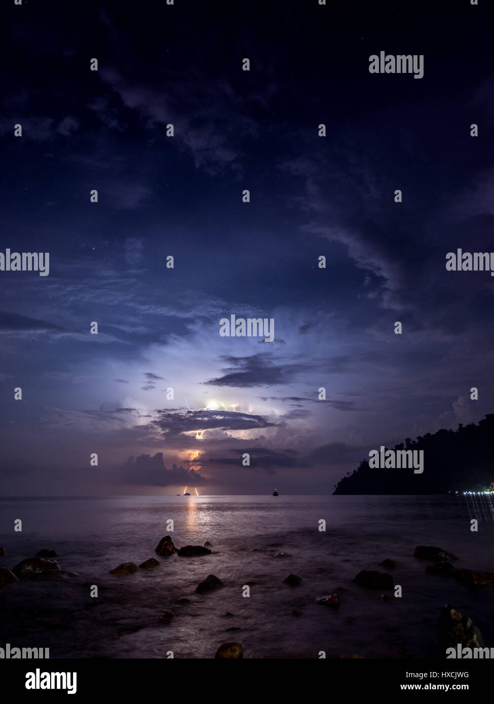 A lightening storm lighting up the night sky in the distance as viewed from the ABC beach on Tioman Island, Malaysia. - Stock Image