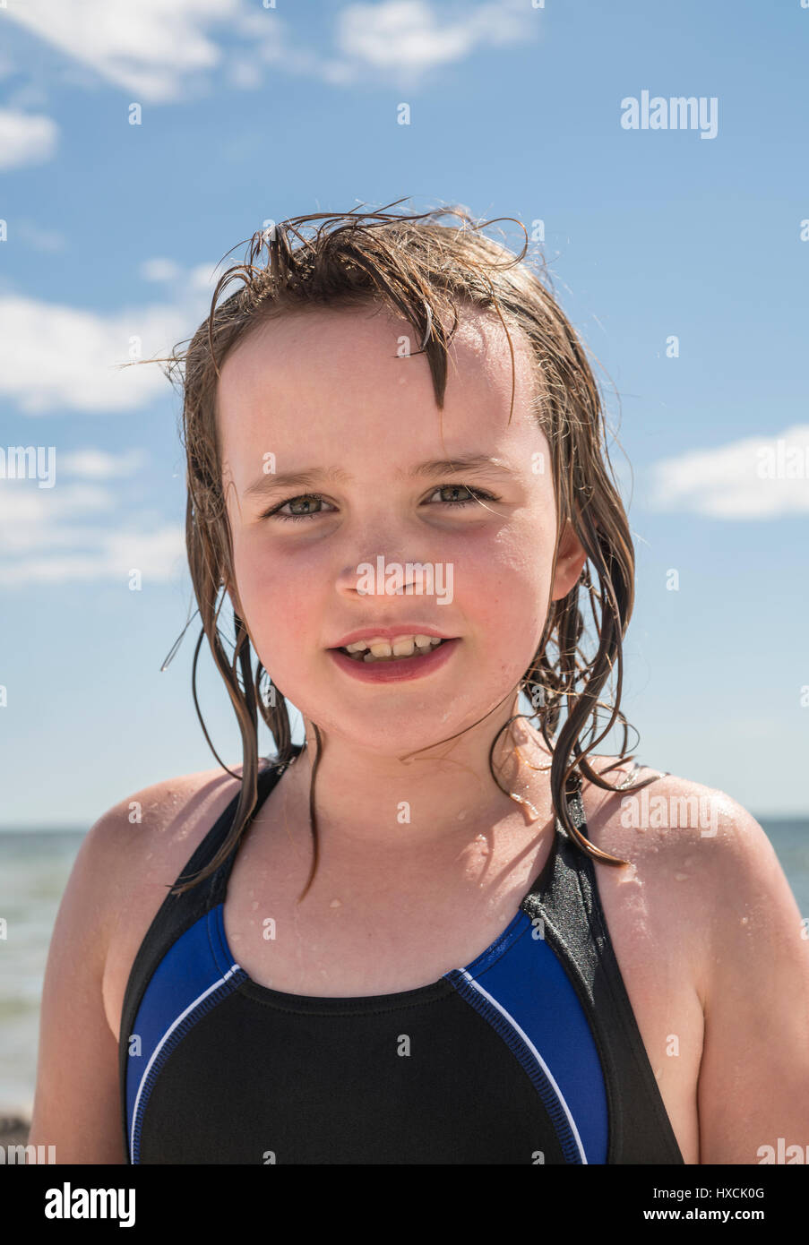 Portrait of a wet young girl in bathing suit at a beach in the summer. Face only with clear blue sky with white - Stock Image