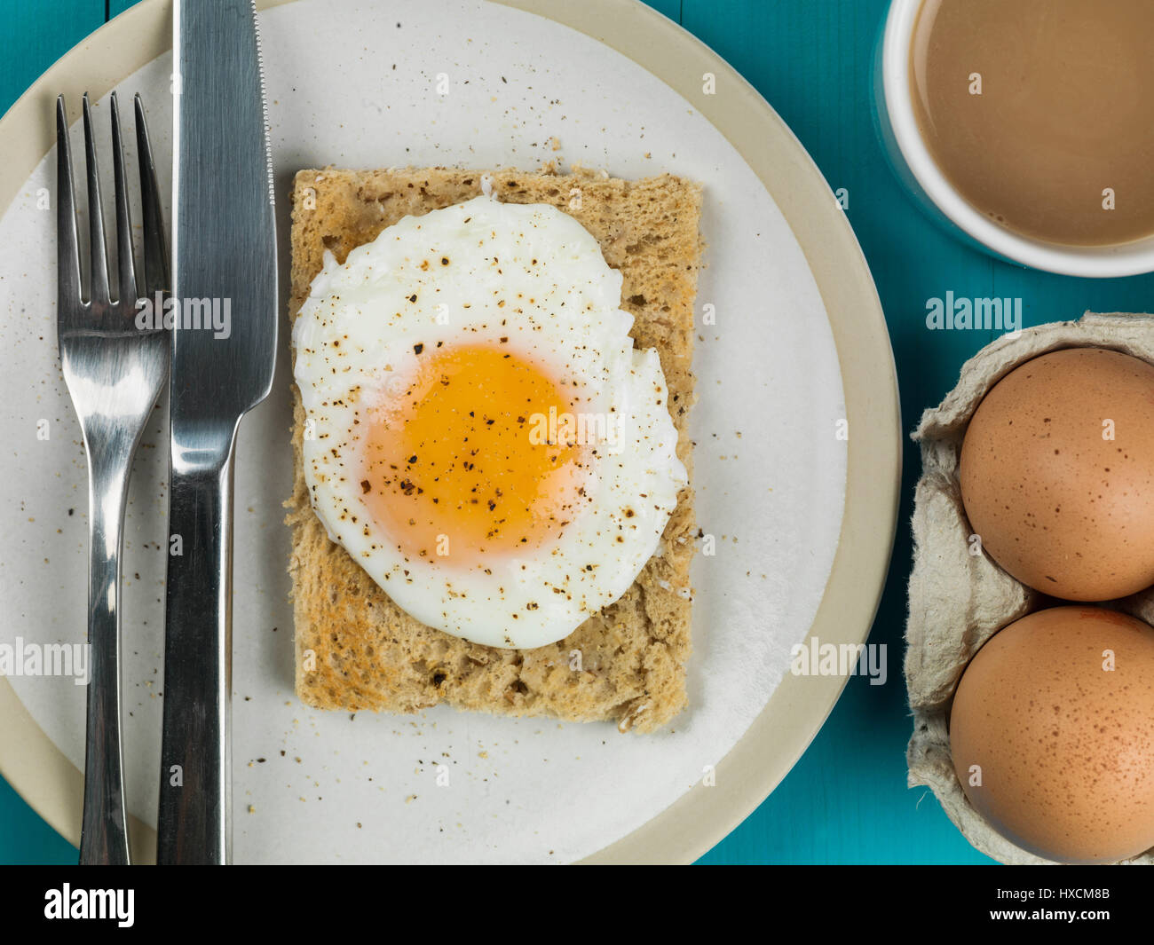 Poached Egg on Toasted Bread Breakfast Food With a Mug of Tea or Coffee and Two Raw Eggs - Stock Image