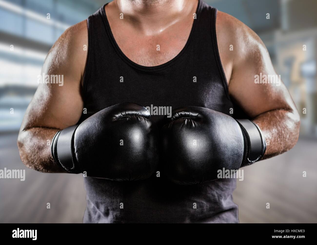 Digital composite of Man with boxing gloves mid sections against blurry gym - Stock Image