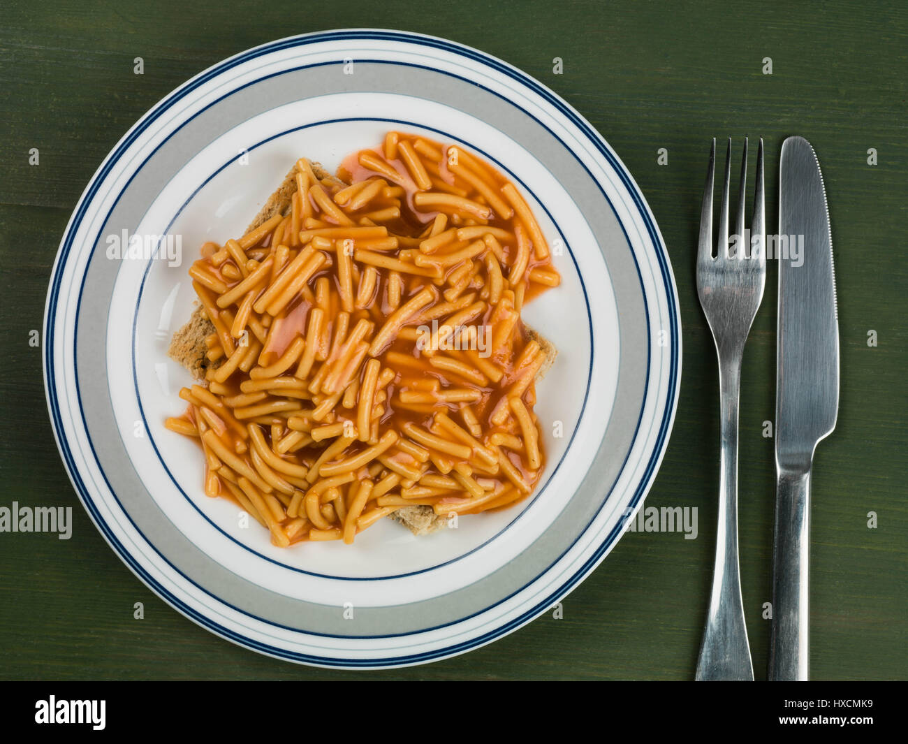 Spaghetti on Toasted Bread Served on a Plate Against a Green background - Stock Image