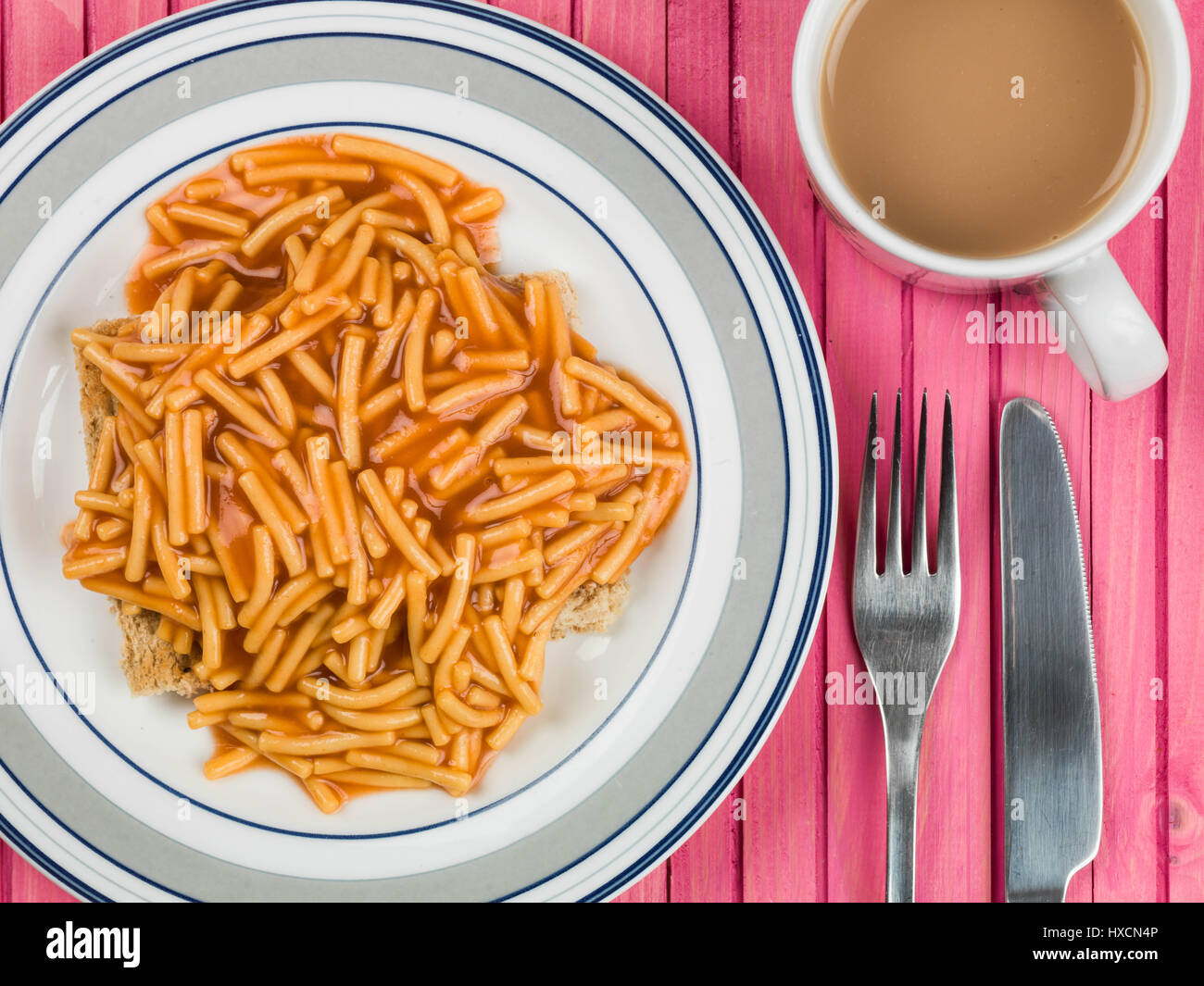 Spaghetti on Toasted Bread Served on a Plate With a Mug of Tea or Coffee - Stock Image